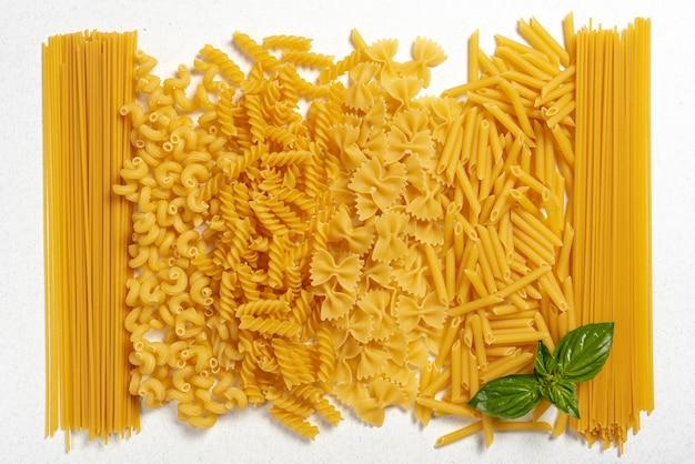 Vista superior de diferentes tipos de macarrão no fundo liso Foto gratuita