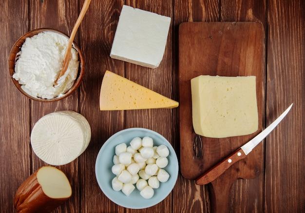 Vista superior de diferentes tipos de queijo na mesa de madeira rústica Foto gratuita