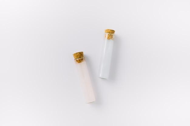 Vista superior de dois tubos de ensaio de óleo essencial na superfície branca Foto gratuita
