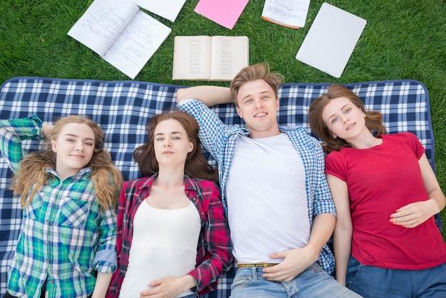 Vista superior, de, estudantes, mentindo, ligado, cobertor piquenique Foto gratuita