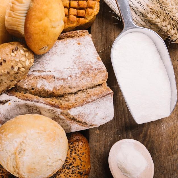 Vista superior, de, farinha, em, pá, com, assado, inteiro, pães, e, bolo, ligado, tabela madeira Foto gratuita