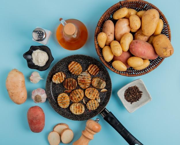 Vista superior de fatias de batata frita na frigideira com as cozidas na maionese de cesta alho sal pimenta e manteiga em azul Foto gratuita