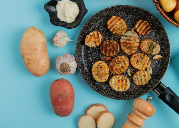 Vista superior de fatias de batata frita na frigideira com sal de alho cru maionese um no azul Foto gratuita