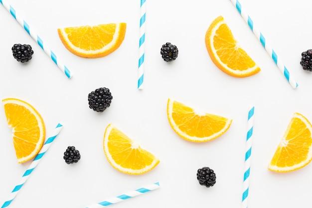 Vista superior de fatias de laranja e amoras com canudos para suco Foto Premium