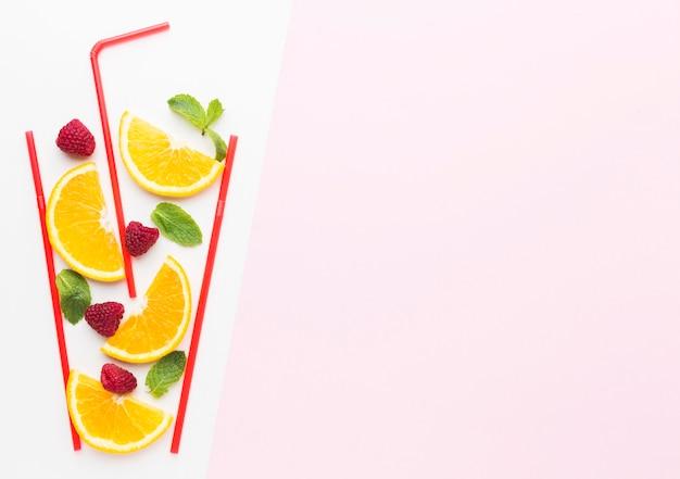 Vista superior de fatias de laranja em vidro de palha com espaço de hortelã e cópia Foto Premium