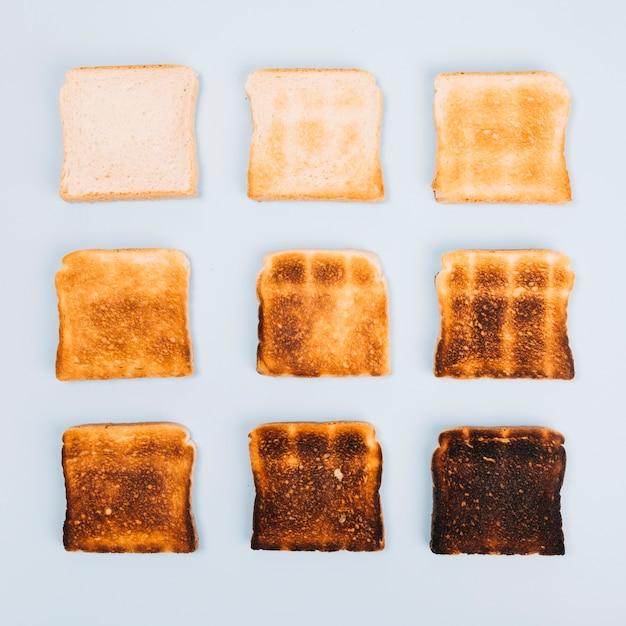 Vista superior de fatias de pão em diferentes estágios de brindar em fundo branco Foto gratuita