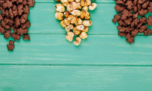 Vista superior de flocos de milho crocantes de chocolate e pipoca de caramelo sobre fundo verde, com espaço de cópia Foto gratuita