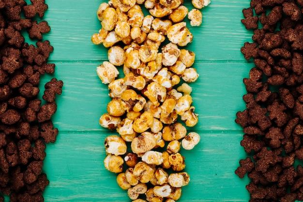Vista superior de flocos de milho crocantes de chocolate e pipoca de caramelo sobre fundo verde de madeira Foto gratuita