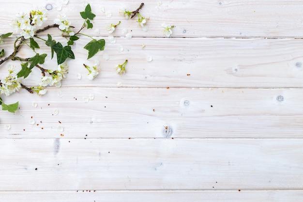 Vista superior de flores brancas da primavera e folhas em uma mesa de madeira com espaço para seu texto Foto gratuita