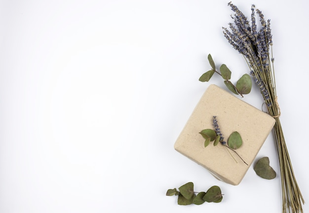 Vista superior de flores de lavanda com caixa de presente marrom contra isolado no fundo branco Foto gratuita