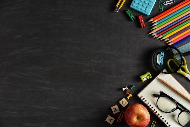 Vista superior de fontes dos artigos de papelaria ou de escola com livros, lápis da cor, calculadora, portátil, grampos e maçã vermelha no fundo do quadro. Foto Premium