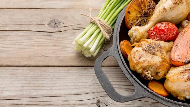 Vista superior de frango assado e vegetais na panela com cebolinha Foto Premium