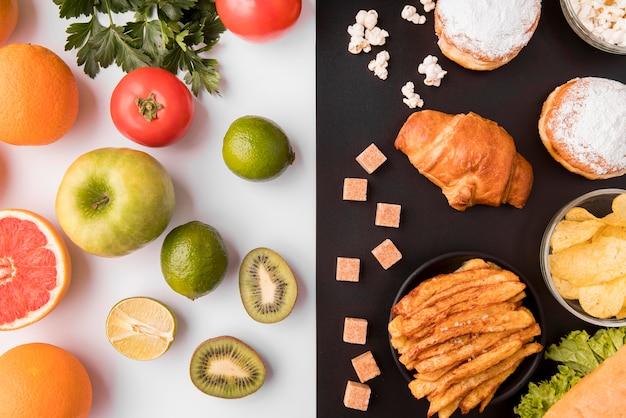 Vista superior de frutas e legumes versus alimentos não saudáveis Foto gratuita