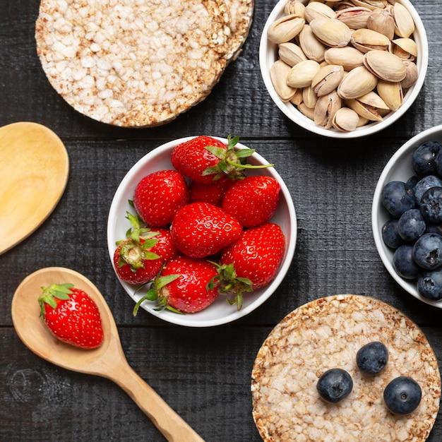 Vista superior de frutas e pistache em tigelas Foto gratuita