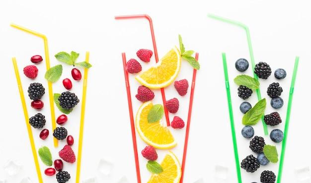 Vista superior de frutas em copos de palha com hortelã Foto Premium
