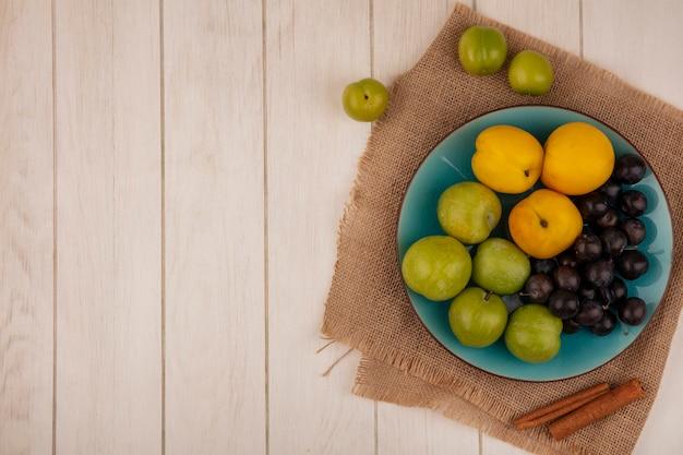 Vista superior de frutas frescas, como pêssegos de cereja verde em um prato azul em um pano de saco em um fundo branco de madeira com espaço de cópia Foto gratuita
