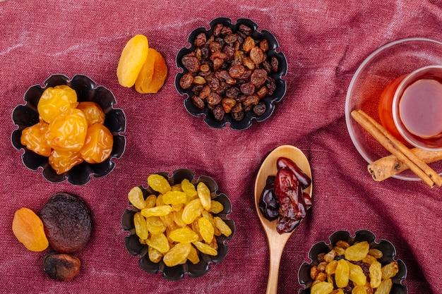 Vista superior de frutas secas, ameixas de cereja, passas, damascos e datas secas em latas de mini torta servidas com chá sobre fundo de cor vermelho escuro Foto gratuita