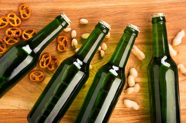 Vista superior de garrafas de cerveja com lanches Foto gratuita