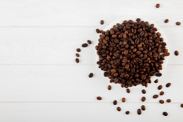 Vista superior de grãos de café em um prato fundo branco, com espaço de cópia Foto gratuita