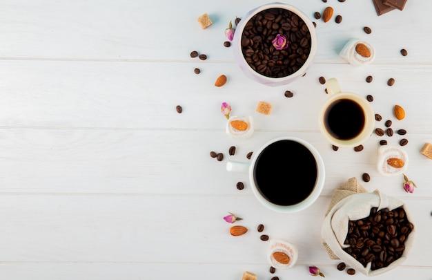 Vista superior de grãos de café em um saco e xícaras de café sobre fundo branco, com espaço de cópia Foto gratuita
