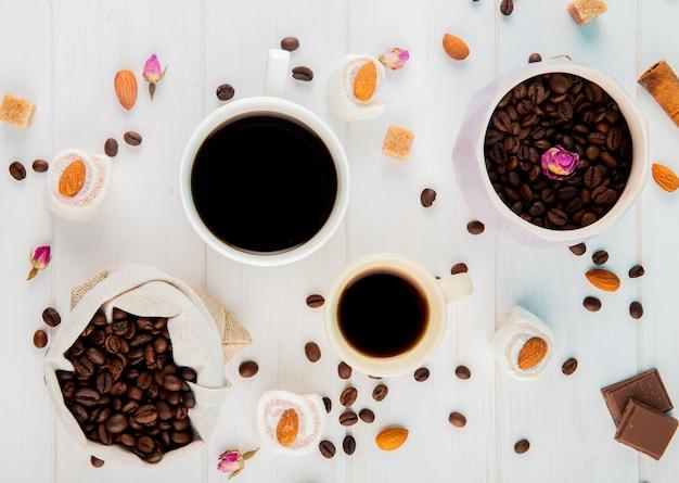 Vista superior de grãos de café em um saco e xícaras de café sobre fundo branco Foto gratuita