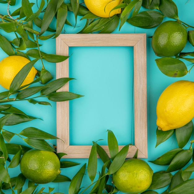 Vista superior de gresh limões verdes e amarelos com folhas na superfície azul Foto gratuita