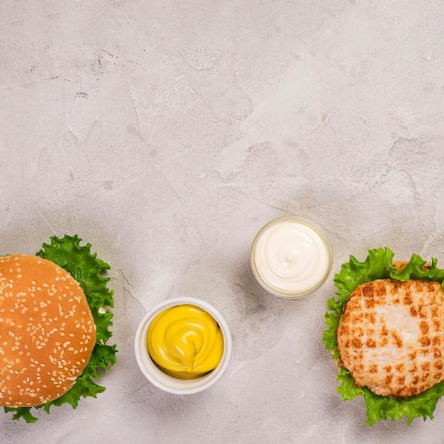 Vista superior de hambúrgueres com molho de mostarda e maionese Foto gratuita