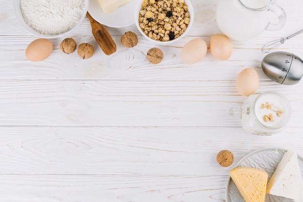 Vista superior de ingredientes alimentares saudáveis e ferramentas na mesa de madeira branca Foto gratuita
