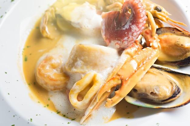 Vista superior de ingredientes de alimentos de fusão com porcaria, mexilhões, camarão e lula vermelha pored com whi Foto Premium