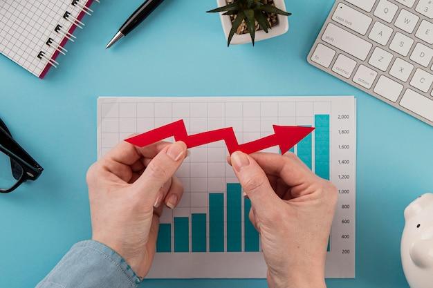 Vista superior de itens de negócios com gráfico de crescimento e mãos segurando setas Foto gratuita