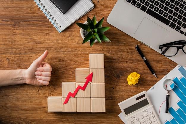 Vista superior de itens de negócios e seta de crescimento com a mão levantando os polegares Foto Premium