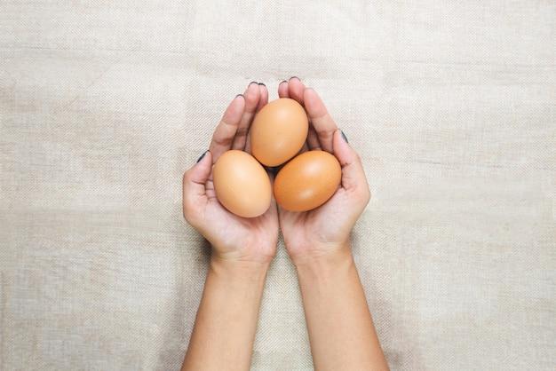Vista superior, de, jovem, mulher, mãos, segurando, ovos, em, mãos, ligado, saco Foto Premium
