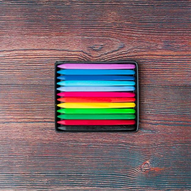 Vista superior de lápis de cera coloridos na mesa de madeira Foto gratuita
