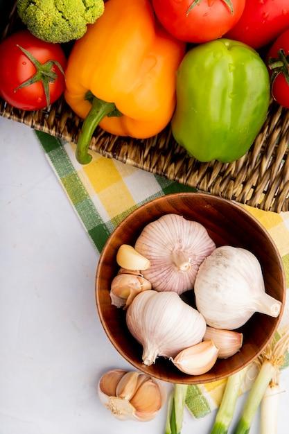 Vista superior de legumes como alho, pimentão e tomate na cesta de vime Foto gratuita