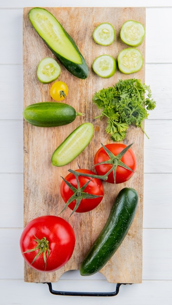 Vista superior de legumes como coentro de tomate pepino na tábua de madeira Foto gratuita