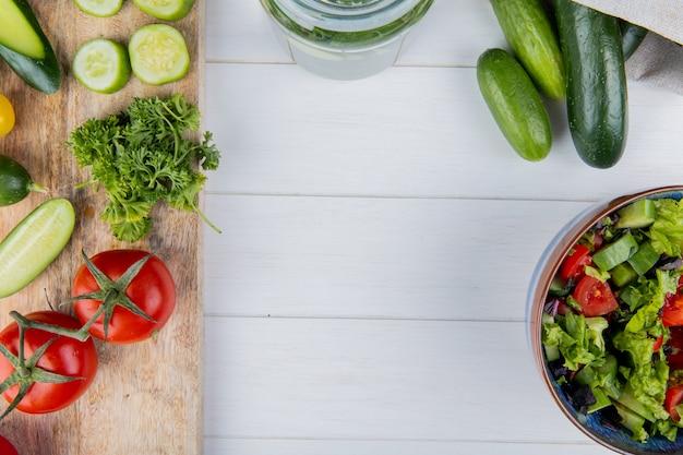 Vista superior de legumes como coentro de tomate pepino na tábua e pepinos em saco com salada de legumes na madeira com espaço de cópia Foto gratuita