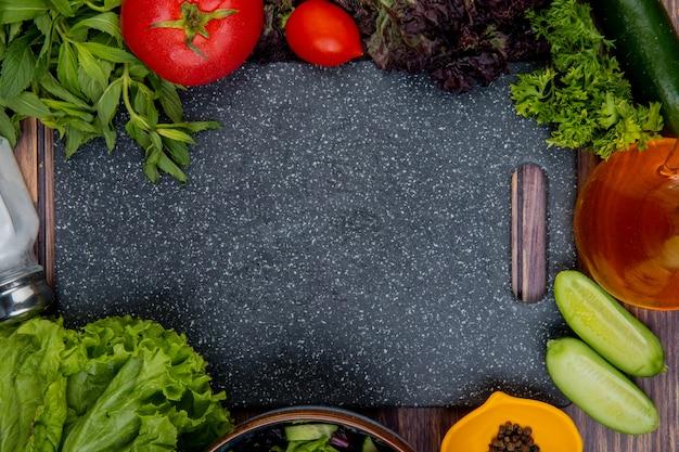 Vista superior de legumes cortados e inteiros como tomate manjericão hortelã pepino alface coentro com sal pimenta do reino e tábua de madeira Foto gratuita