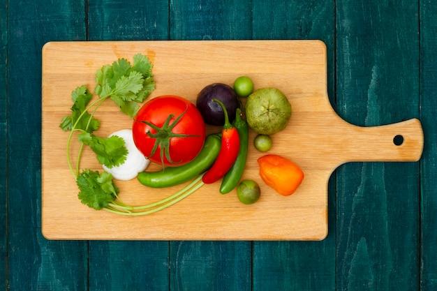 Vista superior de legumes em uma placa de corte Foto gratuita