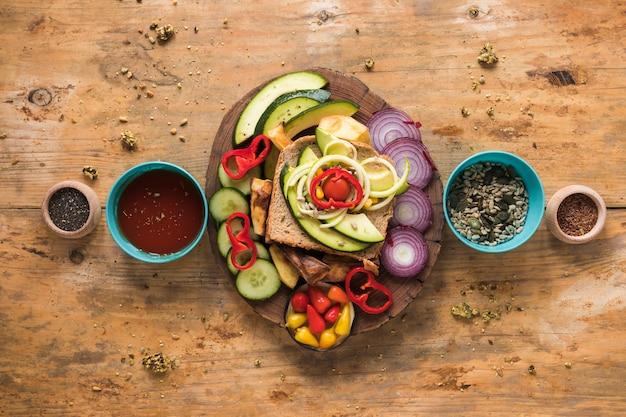 Vista superior de legumes frescos e ingredientes para sanduíche, dispostas em pano de fundo de madeira Foto gratuita