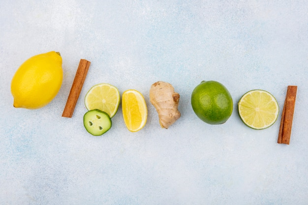 Vista superior de limões frescos e coloridos com bastões de canela e gengibre com fatias de pepino em branco Foto gratuita