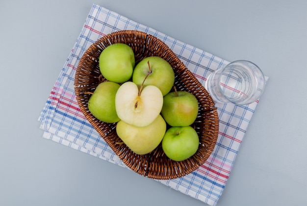 Vista superior de maçãs verdes na cesta e copo de água no pano xadrez e fundo cinza Foto gratuita