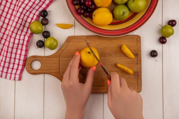 Vista superior de mãos femininas cortando pêssego em um javali de madeira com faca e frutas como ameixas cereja verdes isoladas em um fundo branco de madeira Foto gratuita