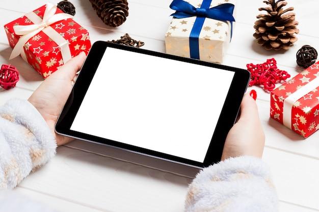Vista superior de mãos femininas segurando um tablet em fundo de natal de madeira Foto Premium