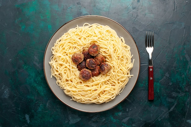 Vista superior de massa italiana cozida com almôndegas na superfície azul escura Foto gratuita