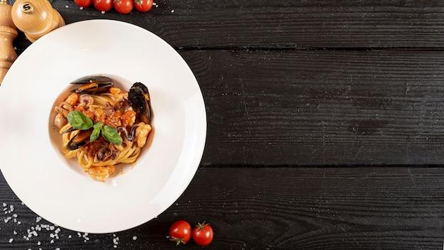 Vista superior de massas e frutos do mar na mesa de madeira Foto gratuita