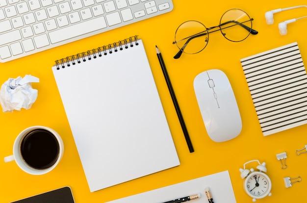 Vista superior de material de escritório com mouse e óculos Foto Premium