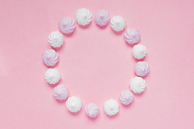 Vista superior de merengues torcidos brancos e rosa em rosa Foto Premium