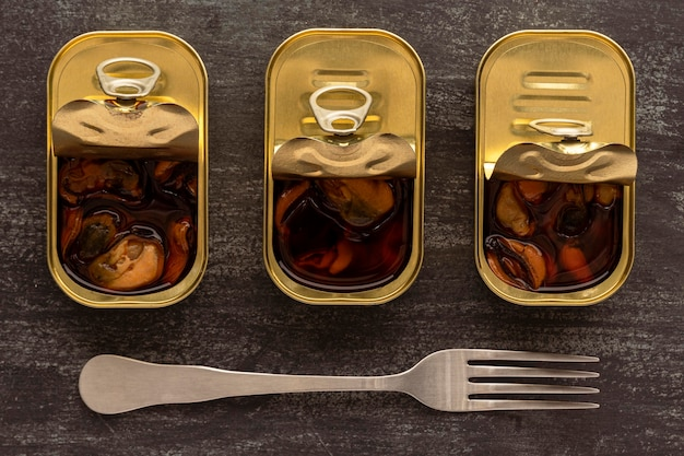 Vista superior de mexilhões preservados em latas com garfo Foto gratuita