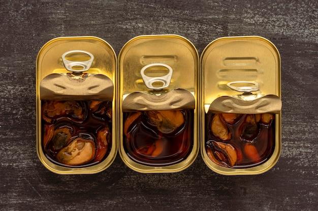 Vista superior de mexilhões preservados em latas Foto gratuita