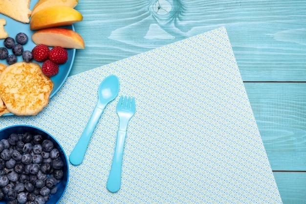 Vista superior de mirtilos com talheres e frutas Foto gratuita